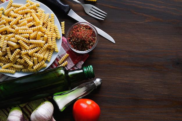 Pâtes, huile d'olive, épices, tomates, sel, ail, couteau et fourchette se trouvent sur une table en bois sombre. vue de dessus
