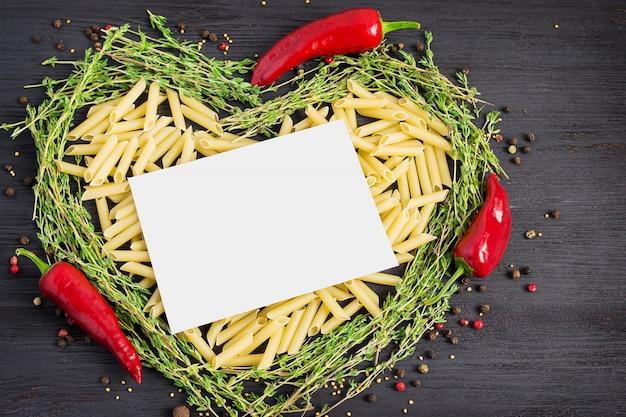 Pâtes et ingrédients italiens sur fond sombre.