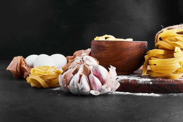 Pâtes avec des ingrédients mélangés autour.