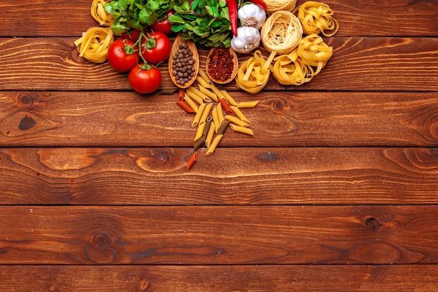 Pâtes et ingrédients sur une table en bois avec fond d'espace copie. vue de dessus.