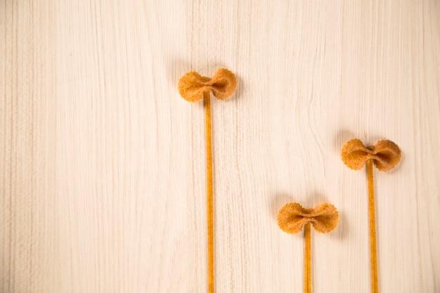 Pâtes intégrales de forme entière avec des fleurs sur une table en bois blanc
