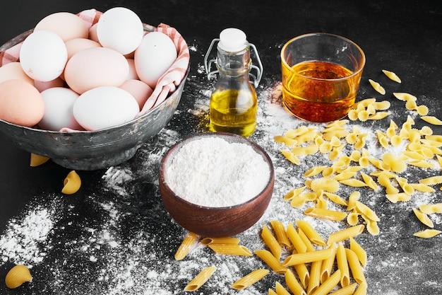 Pâtes isolées sur une surface recouverte de farine avec des ingrédients de côté.