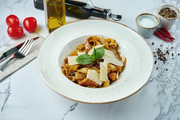 Pâtes italiennes appétissantes au saumon, tomates séchées au soleil et parmesan dans une assiette blanche sur une surface en marbre