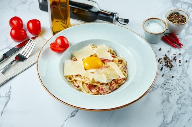 Pâtes italiennes appétissantes carbonara avec sauce blanche, jaune, bacon et parmesan dans une assiette blanche sur une surface en marbre