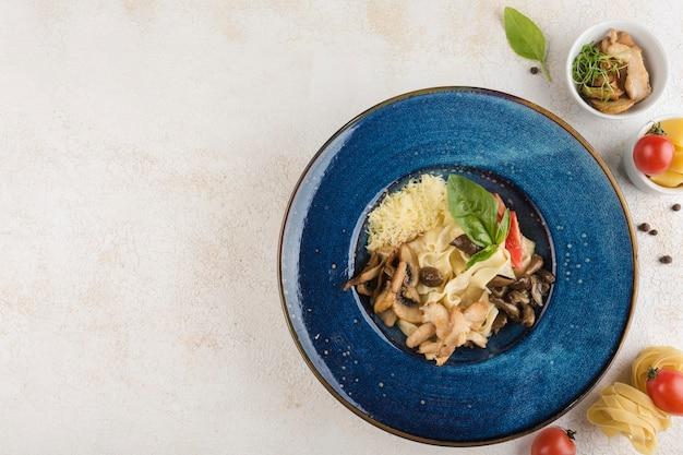 Pâtes italiennes au poulet et champignons sur une assiette bleue avec une serviette sur fond clair. vue de dessus avec un espace de copie pour le texte. nourriture du restaurant. orientation horizontale.