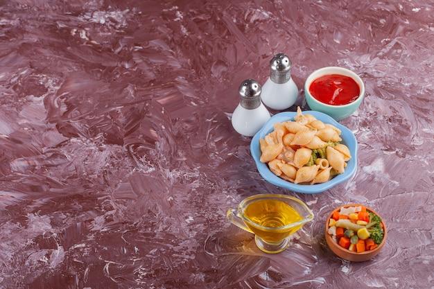 Pâtes italiennes aux coquillages avec sauce tomate et salade de légumes sur table lumineuse.