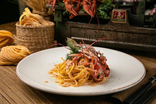 Pâtes italiennes aux écrevisses bouillies et sauce sur une table de ferme en bois