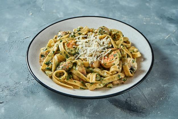 Pâtes italiennes aux fruits de mer, crevettes et parmesan dans une assiette grise sur fond gris. mise au point sélective, gros plan