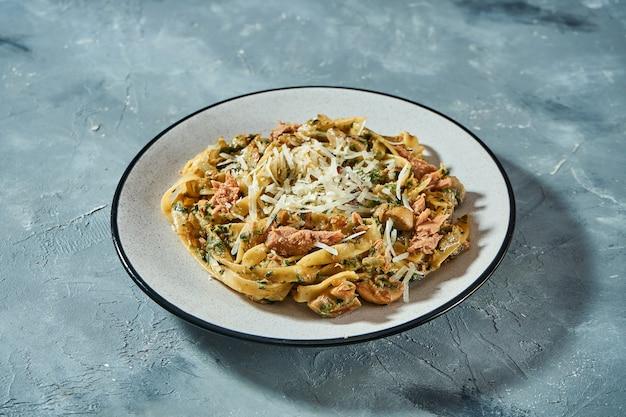 Pâtes italiennes aux fruits de mer, thon en conserve et parmesan dans une assiette grise sur fond gris. gros plan, mise au point sélective