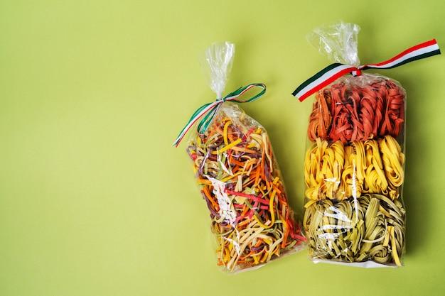 Pâtes italiennes brutes colorées dans un sac en plastique transparent sur fond vert. pâtes colorées faites maison.