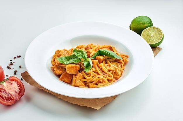 Pâtes italiennes classiques (spaghetti) aux fruits de mer, saumon et sauce rouge dans une assiette blanche sur une assiette blanche