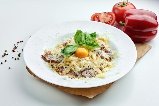 Pâtes italiennes classiques (spaghetti) carbonara avec bacon, jaune, parmesan dans une assiette blanche sur une assiette blanche
