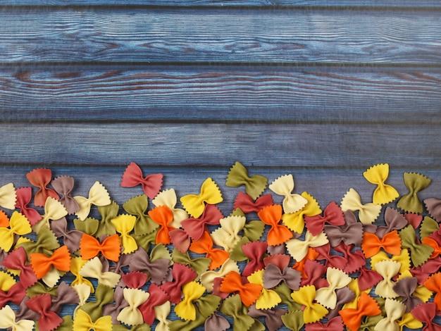 Pâtes italiennes colorées sèches farfalle ou arcs sur fond en bois bleu foncé.
