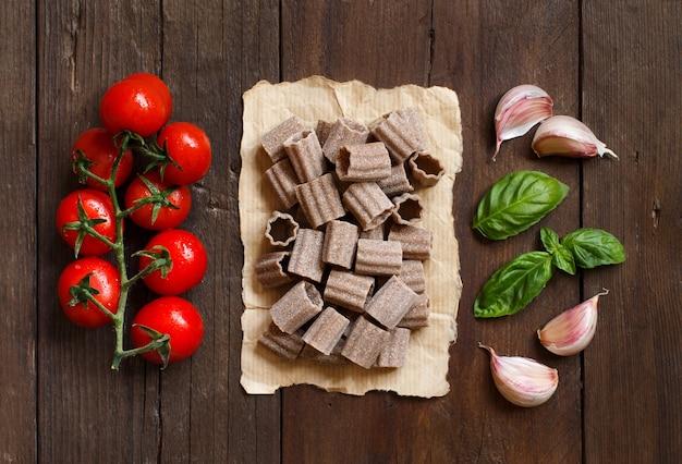 Pâtes italiennes crues, basilic et légumes sur table en bois