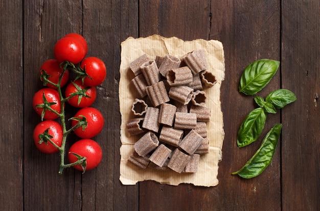 Pâtes italiennes crues, basilic et tomates cerises sur table en bois