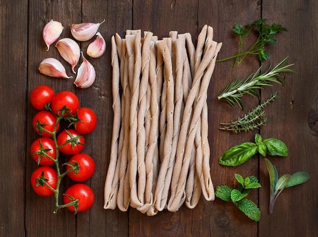 Pâtes italiennes crues, herbes et légumes sur table en bois