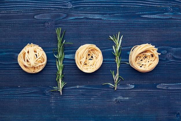 Pâtes italiennes crues sur table en bois bleu foncé, vue de dessus