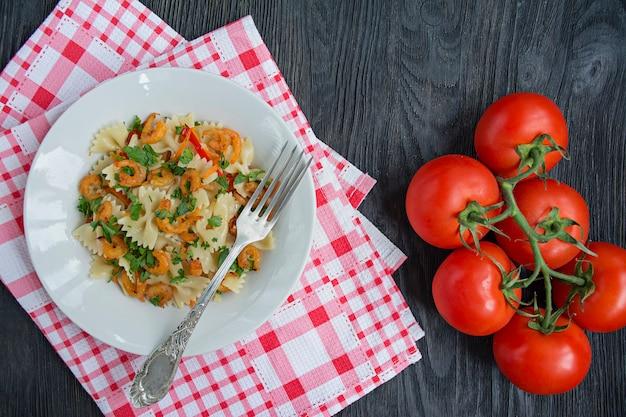 Pâtes italiennes dans une sauce aux crevettes sur une assiette, vue de dessus.