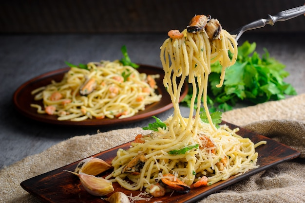 Pâtes italiennes dans une sauce crémeuse aux fruits de mer, crevettes et moules sur une assiette