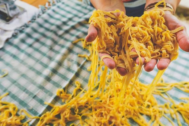 Pâtes italiennes faites maison, mains d'une personne faisant des pâtes fraîches