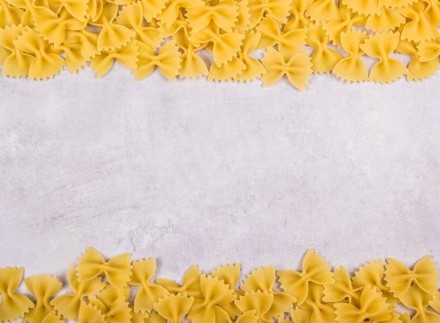 Pâtes italiennes farfalle sur fond gris
