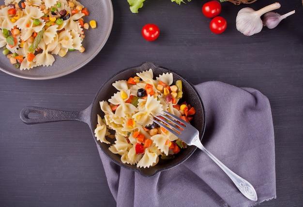 Pâtes italiennes farfalle avec mélange de légumes sur une poêle en fer noir sur fond noir. vue de dessus.