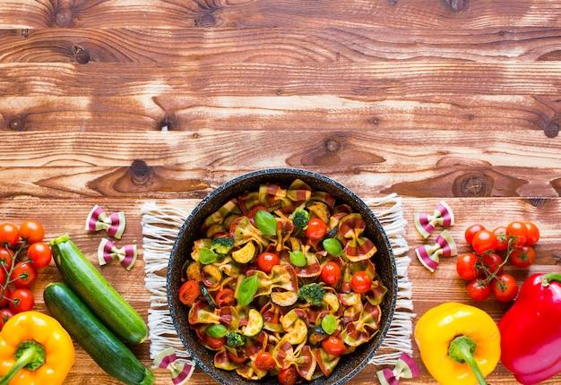 Pâtes italiennes farfalle à la sauce tomate et divers types de légumes sur un fond en bois