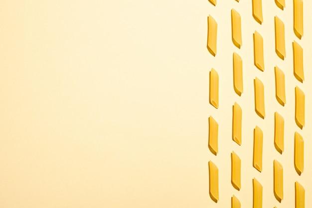 Pâtes italiennes, macaroni au tube de penne cru sur la table de crème jaune, vue de dessus copie espace, nourriture abstraite