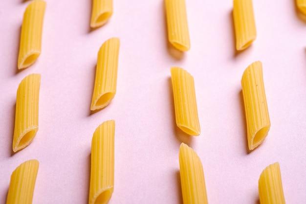 Pâtes italiennes, macaroni tube penne cru sur fond rose