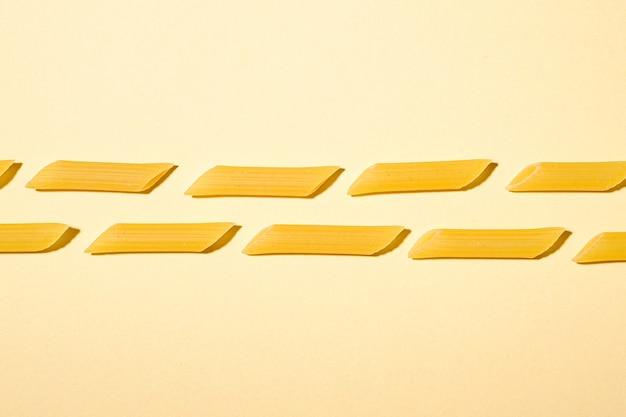 Pâtes italiennes, modèle de macaroni tube penne cru sur mur crème jaune, vue de dessus copie espace, nourriture abstraite