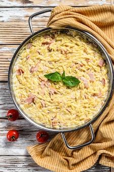 Pâtes italiennes orzo. recette avec sauce à la crème, bacon et basilic. risoni préparé. fond en bois blanc. vue de dessus