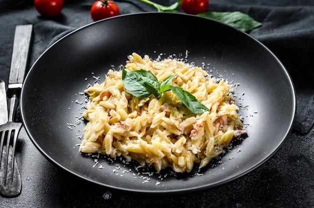 Pâtes italiennes orzo. recette avec sauce à la crème, bacon et basilic. risoni préparé. fond en bois noir. vue de dessus