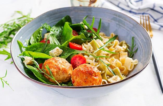 Pâtes italiennes. pâtes aux boulettes de viande, fromage et salade fraîche