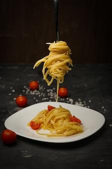 Pâtes italiennes sur une plaque sur un fond sombre avec des tomates cerises