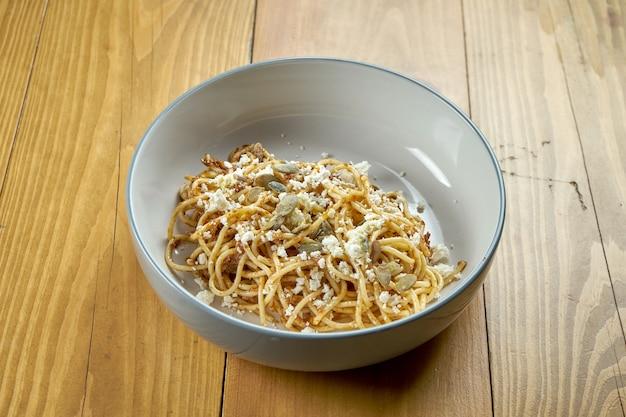 Pâtes italiennes (spaghetti) au pesto, fromage feta et graines de citrouille. plat végétarien