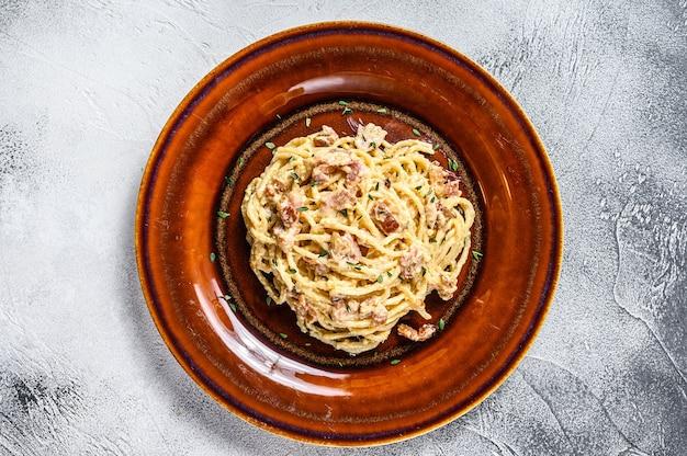 Pâtes italiennes spaghetti carbonara avec bacon, fromage parmesan à pâte dure et sauce à la crème. vue de dessus.