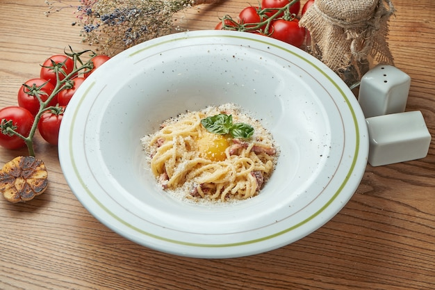 Pâtes italiennes-spaghetti carbonara avec bacon et jaune, fromage parmesan, servi dans une assiette blanche sur une table en bois. cuisine italienne