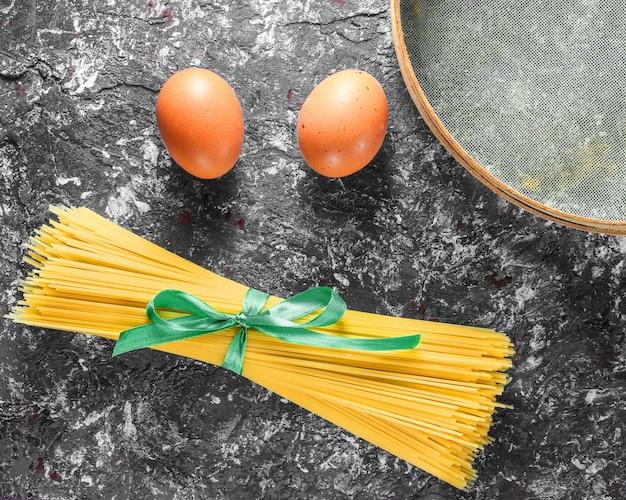 Pâtes italiennes, tamis, œufs sur fond de béton gris