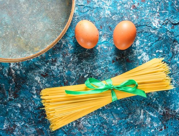 Pâtes italiennes, tamis, œufs sur une table en béton bleu. processus de cuisson. vue de côté