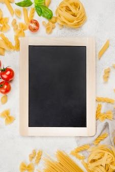 Pâtes italiennes et tomates à côté du tableau noir