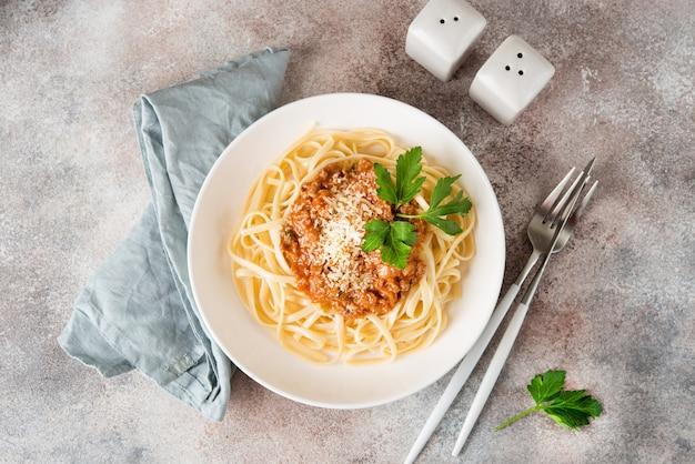 Pâtes italiennes traditionnelles avec sauce bolognaise dans une assiette blanche, vue du dessus