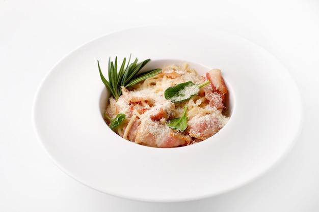 Pâtes italiennes avec des tranches de poulet à la viande, du pesto de fromage et des feuilles vertes sur une large assiette blanche vue de dessus sur fond blanc
