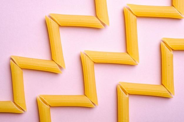 Pâtes italiennes, tube penne cru macaroni motif en zigzag sur mur rose, vue de dessus, nourriture abstraite