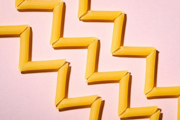 Pâtes italiennes, tube de penne cru macaroni zigzag sur fond rose, vue de dessus, nourriture abstraite