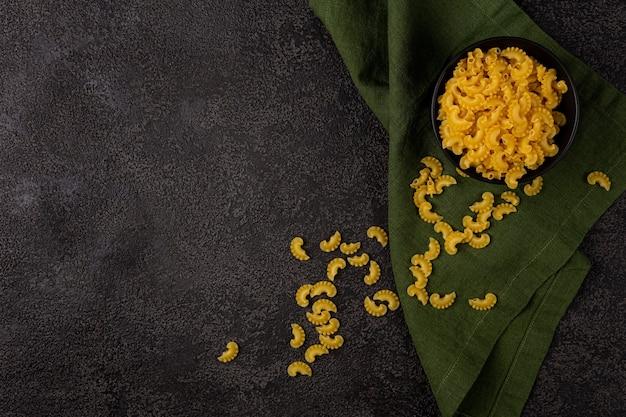 Pâtes jaunes crues dans un petit bol sur un fond structurel sombre avec un espace pour copier. vue de dessus. espace de copie