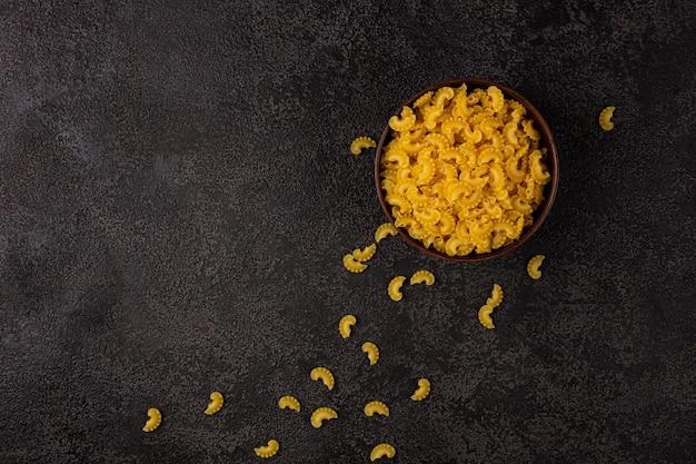Pâtes jaunes crues dans un petit bol sur un fond structurel sombre avec un espace pour copier