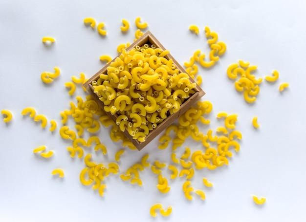 Pâtes jaunes non cuites sur le fond blanc.