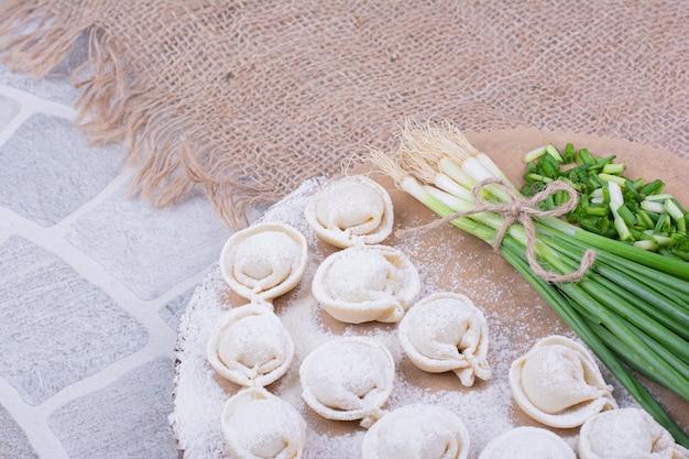 Pâtes khinkali crues sur farine avec un bouquet d'oignon vert.