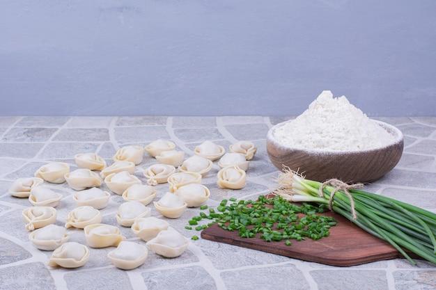 Pâtes de khinkali crues sur la farine avec un bouquet d'oignon vert.