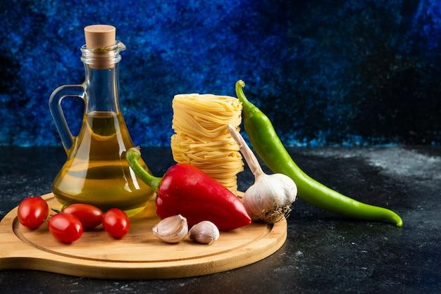 Pâtes et légumes non cuits sur planche de bois avec de l'huile.